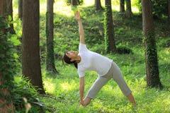 Japanese woman doing yoga triangle pose Stock Photo