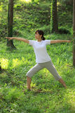 Japanese woman doing yoga warrior II pose Royalty Free Stock Image