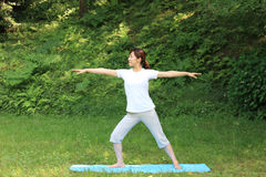 Japanese woman doing yoga warrior II pose Royalty Free Stock Photos