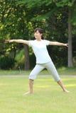 Japanese woman doing yoga warrior II pose Stock Photo