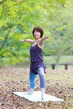 Japanese Woman Doing YOGA warrior II pose Stock Images