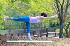 Japanese Woman Doing YOGA warrior III pose. Portrait of Japanewe woman doing yoga exercise outdoor Stock Photography