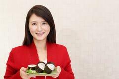 Japanese woman eating sushi. Woman who eats sushi rolls royalty free stock image