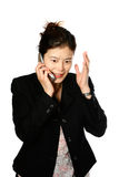 Japanese woman frustrated. Young Japanese businesswoman expressing shock or anger while being on her mobile phone, isolated on white Royalty Free Stock Photography