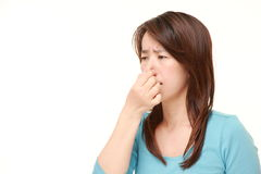 Japanese woman holding her nose because of a bad smell. Studio shot of Japanese woman on white background stock image