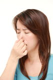 Japanese woman holding her nose because of a bad smell Stock Photos
