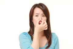 Japanese woman holding her nose because of a bad smell. Studio shot of Japanese woman on white background royalty free stock photography
