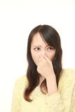 Japanese woman holding her nose because of a bad smell Stock Photography
