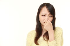 Japanese woman holding her nose because of a bad smell. Studio shot of young Japanese woman's portrait on white background stock photography