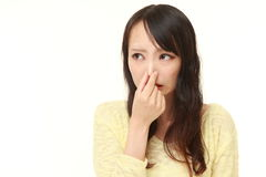 Japanese woman holding her nose because of a bad smell. Studio shot of young Japanese woman's portrait on white background stock image