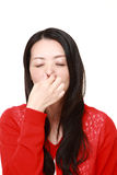 Japanese woman holding her nose because of a bad smell. Studio shot of young Japanese woman on white background royalty free stock photography
