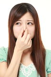 Japanese woman holding her nose because of a bad smell. Studio shot of young Japanese woman on white background stock photography