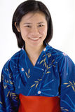 Japanese woman in kimono. Happy young Japanese woman in traditional blue kimono, isolated on white background Royalty Free Stock Photos