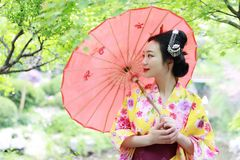 Traditional Asian Japanese beautiful Geisha woman wears kimono bride with a red umbrella in a graden. Japanese woman with kimono Japanese bride smiling stand by Stock Photo