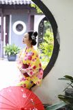 Traditional Asian Japanese beautiful Geisha woman wears kimono reading book in a summer nature. Japanese woman with kimono Japanese bride smiling stand by bamboo Stock Photography