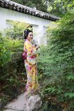 Traditional Asian Japanese beautiful Geisha woman wears kimono in a summer nature. Japanese woman with kimono Japanese bride smiling stand by bamboo in a spring Royalty Free Stock Photo