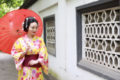 Traditional Asian Japanese beautiful Geisha bride woman wears kimono hold a umbrella in a summer nature garden. Japanese woman with kimono Japanese bride smiling Royalty Free Stock Images