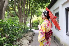 Traditional Asian Japanese beautiful bride Geisha woman wears kimono hold a white red umbrella in a summer nature garden Stock Image