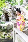 Traditional Asian Japanese beautiful woman bride wears kimono with white umbrella stand by bamboo in outdoor spring garden. Japanese woman with kimono Japanese Stock Image
