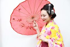 Japanese woman with kimono Japanese bride smiling white background. Japanese bride wearing a yellow kimono and carrying a red umbrella poses outdoors under a Royalty Free Stock Photos