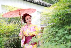 Traditional Asian Japanese beautiful Geisha woman bride wears kimono hold a red umbrella in a summer nature. Japanese woman with kimono Japanese bride smiling Royalty Free Stock Photos