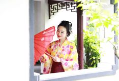 Traditional Asian Japanese beautiful Geisha woman bride wears kimono hold a red umbrella in a summer nature. Japanese woman with kimono Japanese bride smiling Stock Images