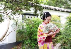 Traditional Asian Japanese beautiful Geisha woman wears kimono hold a fan on hand in a summer nature. Japanese woman with kimono Japanese bride smiling stand by Royalty Free Stock Images