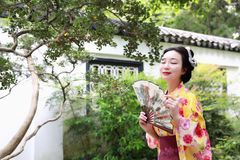 Traditional Asian Japanese beautiful Geisha woman wears kimono reading book in a summer nature. Japanese woman with kimono Japanese bride smiling stand by bamboo Stock Images