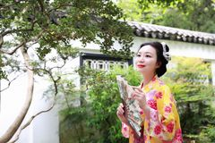 Traditional Asian Japanese beautiful Geisha woman wears kimono reading book in a summer nature. Japanese woman with kimono Japanese bride smiling stand by bamboo Royalty Free Stock Images