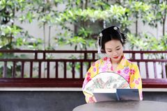 Traditional Asian Japanese beautiful Geisha woman bride wears kimono hold a fan reading book in a summer nature. Japanese woman with kimono Japanese bride Royalty Free Stock Photos