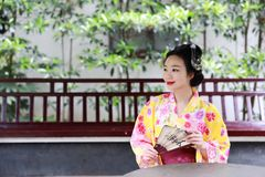 Traditional Asian Japanese beautiful Geisha woman bride wears kimono hold a fan reading book in a summer nature. Japanese woman with kimono Japanese bride Royalty Free Stock Image