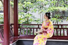 Traditional Asian Japanese beautiful Geisha woman bride wears kimono hold a fan sit on a pavilion in a summer nature. Japanese woman with kimono Japanese bride Royalty Free Stock Image