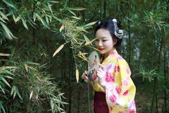 Traditional Asian Japanese beautiful Geisha woman bride wears kimono hold a fan in a summer nature. Japanese woman with kimono Japanese bride smiling stand by Stock Photo