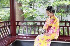 Traditional Asian Japanese beautiful Geisha woman wears kimono sit on a bench in a summer nature garden. Japanese woman with kimono Japanese bride smiling stand Stock Image