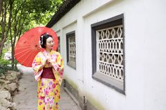 Traditional Asian Japanese beautiful Geisha bride woman wears kimono hold a umbrella in a summer nature garden. Japanese woman with kimono Japanese bride smiling Royalty Free Stock Photography