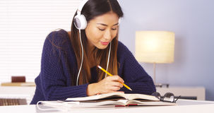 Japanese woman listening to music while doing homework Stock Photo
