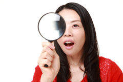 Japanese woman with a magnifying glass Royalty Free Stock Photos