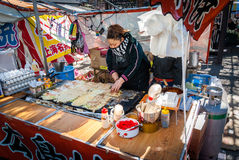 Japanese woman making okonimiyaki. Tokyo, Japan - January 12, 2015: Stall owner making okonomiyaki at a festival in Tokyo Stock Images