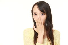 Japanese woman making the speak no evil gesture. Studio shot of young Japanese woman's portrait on white background royalty free stock images