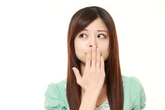 Japanese woman making the speak no evil gesture. Studio shot of young Japanese woman on white background royalty free stock images