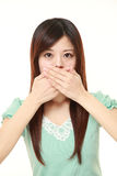 Japanese woman making the speak no evil gesture. Studio shot of young Japanese woman on white background stock photo