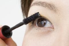Japanese woman making up. LIFESTYLE IMAGE-a Japanese woman's eye making up her eyelashes with mascara stock photography