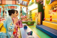 Japanese woman playing hit tumbling dolls stock photos