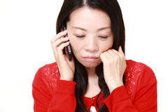 Japanese woman receiving bad news Royalty Free Stock Photo