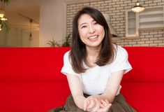 Japanese woman smiling on the sofa at home Royalty Free Stock Photos