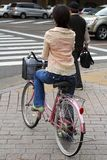 Japanese woman riding bicycle stock photography
