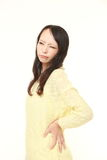 Japanese woman suffers from lumbago. Studio shot of young Japanese woman's portrait on white background Stock Photography