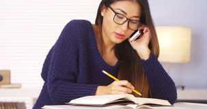 Japanese woman talking on smartphone for homework help Stock Photo