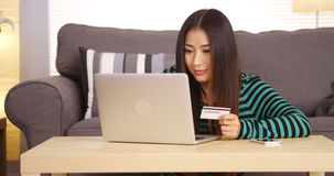 Japanese woman typing in credit card information Stock Image
