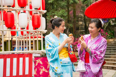 Japanese women going to the local shrine. Tasting delicious dorayaki snacks sharing together enjoy the festival lantern decoration wearing traditional kimono Royalty Free Stock Photography